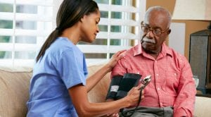 african american woman checking a man's blood pressure